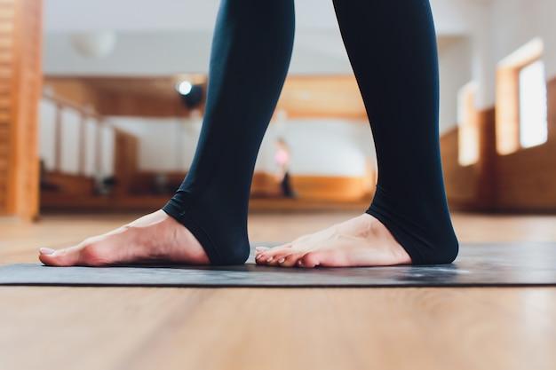 Atrakcyjna szczęśliwa młoda kobieta pracująca w domu out. piękny model robi ćwiczenia jogi na niebieski mat.