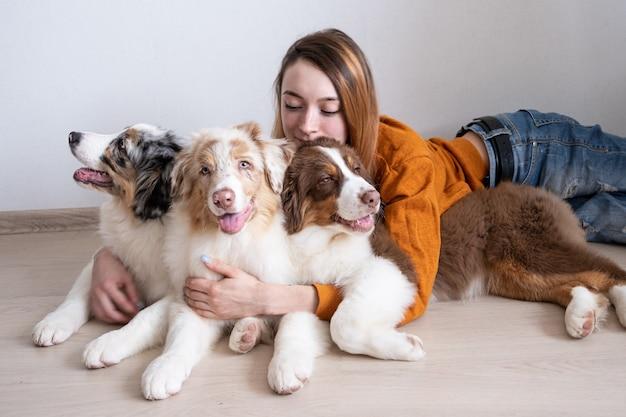 Atrakcyjna szczęśliwa młoda kobieta trzyma trzy małe słodkie owczarek australijski czerwony merle szczeniak. najlepsi przyjaciele. miłość i przyjaźń między człowiekiem a zwierzęciem.