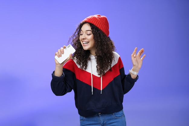 Atrakcyjna szczęśliwa młoda kobieta z kręconymi włosami w kapeluszu śpiewając, ciesząc się idealnym zimowym dniem śpiewając w smartfonie, trzymając telefon komórkowy jak mikrofon, uwielbiam karaoke na niebieskim tle.