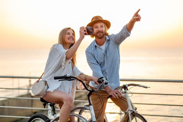 Atrakcyjna szczęśliwa para podróżująca latem na rowerach, mężczyzna i kobieta o blond włosach moda w stylu boho hipster, wspólna zabawa, robienie zdjęć zwiedzanie