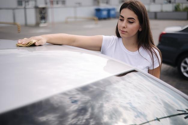 Atrakcyjna, szczęśliwa, radosna kobieta-kierowca wyciera przednią szybę w swoim samochodzie za pomocą szmatki w samoobsługowej myjni samochodowej