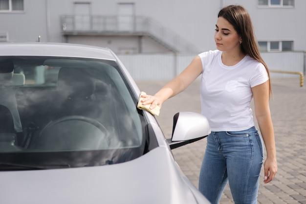 Atrakcyjna szczęśliwa radosna kobieta-kierowca wyciera swój samochód szmatką w samoobsługowej myjni samochodowej