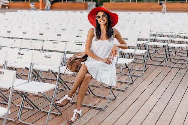 Atrakcyjna szczęśliwa uśmiechnięta kobieta ubrana w białą sukienkę, czerwony kapelusz, okulary przeciwsłoneczne siedzące w samym letnim teatrze na świeżym powietrzu, wiele krzeseł, wiosenny trend w modzie ulicznej, machająca ręką witam
