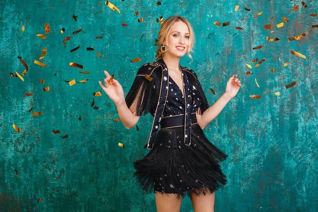 Atrakcyjna szczęśliwa uśmiechnięta kobieta w stylowej czarnej sukni