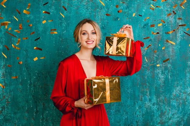 Atrakcyjna szczęśliwa uśmiechnięta kobieta w stylowej czerwonej sukience obchodzi boże narodzenie i nowy rok z prezentami