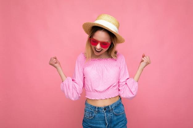 Atrakcyjna szczęśliwa uśmiechnięta młoda blondynka na sobie letnie ubranie i stylowe okulary przeciwsłoneczne na białym tle