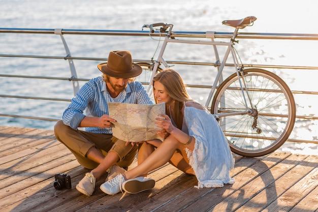 Atrakcyjna szczęśliwa uśmiechnięta para podróżująca latem drogą morską na rowerach, mężczyzna i kobieta z blond włosami w stylu boho hipster, bawiąc się razem, patrząc na zwiedzanie mapy