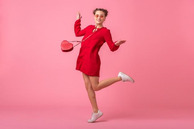 Atrakcyjna szczęśliwa uśmiechnięta stylowa kobieta w czerwonej modnej sukience skaczącej na różowej ścianie na białym tle, trend w modzie wiosna lato, romantyczny nastrój zalotna dziewczyna