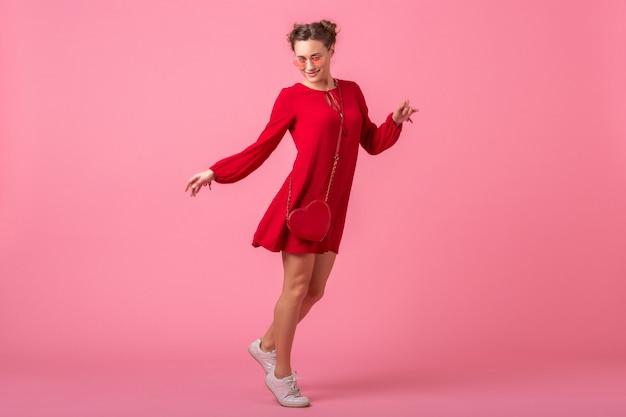 Atrakcyjna szczęśliwa uśmiechnięta stylowa kobieta w czerwonej modnej sukience skoki taniec na różowej ścianie na białym tle, trend w modzie wiosna lato, romantyczny nastrój zalotna dziewczyna