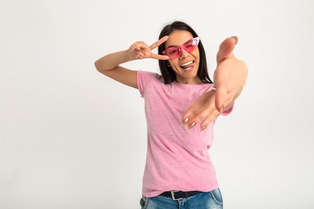 Atrakcyjna szczęśliwa zabawna emocjonalna kobieta w różowej koszulce na białym tle ramiona do przodu