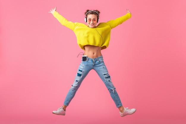 Atrakcyjna szczęśliwa zabawna kobieta skacząca słuchając muzyki w słuchawkach ubrana w kolorowy styl hipster strój na różowej ścianie, ubrany w żółty sweter i okulary przeciwsłoneczne, dobra zabawa