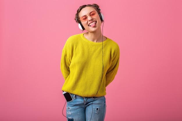 Atrakcyjna szczęśliwa zabawna kobieta słuchająca muzyki w słuchawkach ubrana w strój kolorowy hipster na białym tle na różowej ścianie, ubrany w żółty sweter i okulary przeciwsłoneczne, dobra zabawa