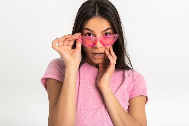 Atrakcyjna szczęśliwa zabawna zaskoczona emocjonalna kobieta w różowej koszulce na białym tle ramiona do przodu zaskoczony zszokowany wyraz twarzy