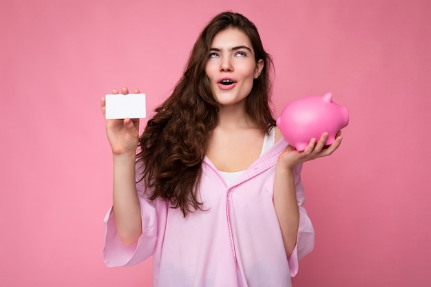 Atrakcyjna szczęśliwa zdziwiona młoda brunetka ubrana w koszulę na białym tle na różowym tle z pustą