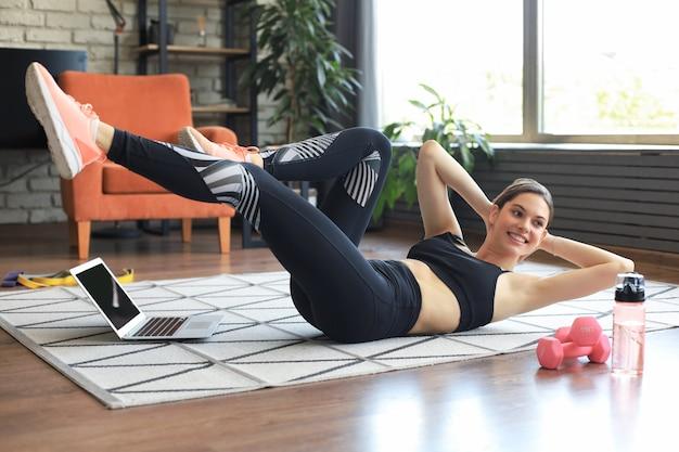 Atrakcyjna, szczupła dziewczyna w sportowej robi ćwiczenia krzyżowe, brzuszki rowerowe stanowią, na podłodze w domu. zdrowy tryb życia.