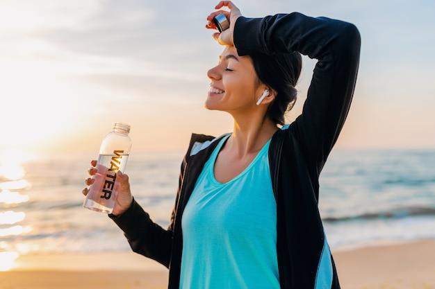 Atrakcyjna szczupła kobieta robi ćwiczenia sportowe na plaży o poranku wschód słońca w stroju sportowym, spragniona woda pitna w butelce, zdrowy tryb życia, słuchanie muzyki na bezprzewodowych słuchawkach, uśmiechanie się szczęśliwe