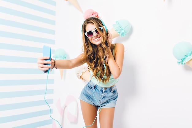 Atrakcyjna, szczupła młoda dama w stylowych okularach przeciwsłonecznych robi selfie pozuje przed ścianą ozdobioną słodyczami. portret słodkie dziewczyny w słuchawkach z niebieskim smartfonem, zabawy w swoim pokoju.