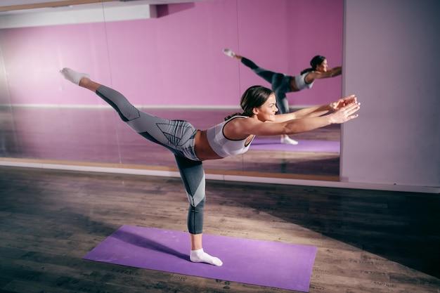 Atrakcyjna szczupła sportowa brunetka rasy kaukaskiej robi nogi wojownik 3 równowagi stojąc na macie w siłowni.