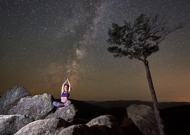 Atrakcyjna szczupła turystyczna dziewczyna siedzi samotnie na wielkim głazie w pozycji lotosu robi joga
