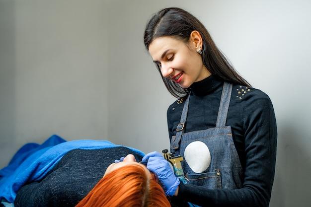 Atrakcyjna tatuażystka z długimi włosami, która tworzy makijaż permanentny i uśmiecha się do pacjenta w salonie spa.