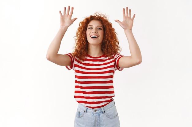 Atrakcyjna towarzyska szczęśliwa europejska rudowłosa kędzierzawa kobieta podnosząca ręce do góry klaskająca przyjaciel dłonie uśmiechnięta szeroko śmiejąca się zabawa ciesząca się zabawnym zabawnym wypoczynkiem, biała ściana