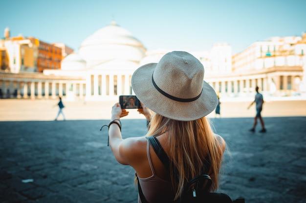 Atrakcyjna turystka dziewczyna w kapeluszu z plecakiem zwiedza latem nowe miasto w europie i robienie zdjęć przy użyciu telefonu