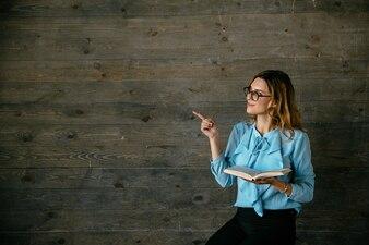 Atrakcyjna uśmiechnięta dziewczyna z książkową seans kopii przestrzenią, patrzeje strona.