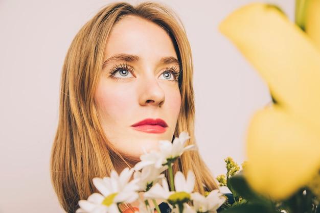 Atrakcyjna ufna marzycielska kobieta z kwiatami