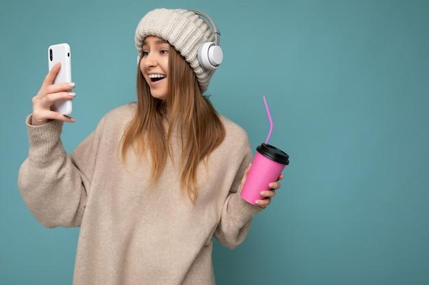 Atrakcyjna uradowana rozkoszna młoda blondynka ubrana w beżowy sweter i beżowy kapelusz biały