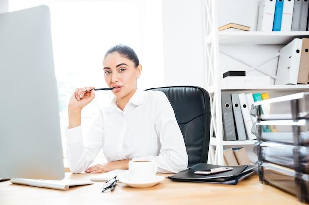 Atrakcyjna, urocza kobieta siedzi w swoim miejscu pracy, trzymając długopis i patrząc na przód