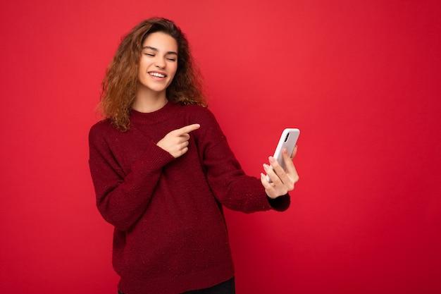 Atrakcyjna, urocza młoda uśmiechnięta szczęśliwa kobieta trzyma telefon komórkowy i przy użyciu telefonu komórkowego, biorąc selfie na sobie stylowe ubrania na białym tle na ścianie