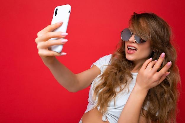 Atrakcyjna, urocza młoda uśmiechnięta szczęśliwa kobieta trzymając telefon komórkowy i za pomocą telefonu komórkowego, biorąc selfie na sobie stylowe ubrania na białym tle na tle ściany.