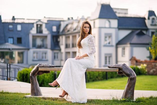 Atrakcyjna, urocza panna młoda siedzi na ławce stylizowanej na ludzkie ręce w hotelu