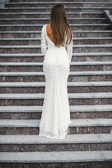 Atrakcyjna urocza panna młoda w białej koronkowej sukni z odkrytymi plecami stojącymi na schodach