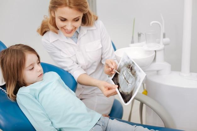 Atrakcyjna, urocza, troskliwa lekarka wyjaśnia swojej małej pacjentce, dlaczego leczy zęby, trzymając skan w dłoni