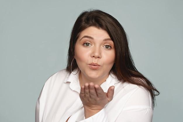 Atrakcyjna, urocza, zalotna młoda kobieta z dodatkową wagą wydymającą usta i wysyłającą ci miłość i buziaki. pulchna figlarna kobieta w białej koszuli dmuchanie pocałunkiem powietrza