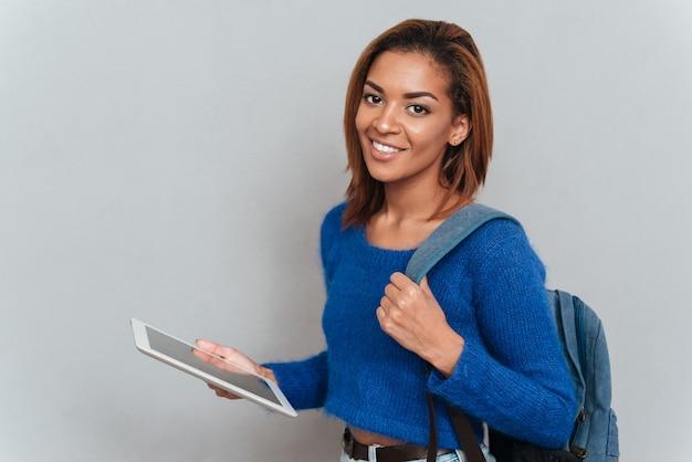 Atrakcyjna uśmiechnięta afrykańska kobieta w swetrze stojąca bokiem z tabletem w ręku i plecakiem na ramieniu