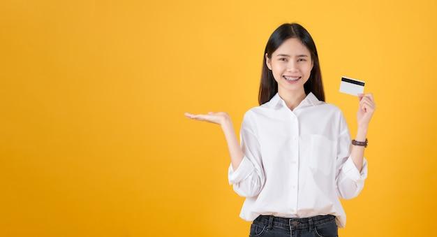 Atrakcyjna uśmiechnięta azjatycka kobieta trzyma kredytową karty zapłatę na żółtym tle z kopii przestrzenią.