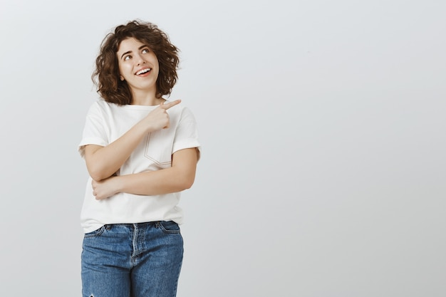 Atrakcyjna uśmiechnięta dziewczyna szuka szczęśliwa i wskazuje prawy górny róg