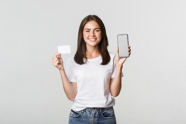 Atrakcyjna uśmiechnięta dziewczyna szuka zadowolonych i pokazuje kartę kredytową, ekran telefonu komórkowego.