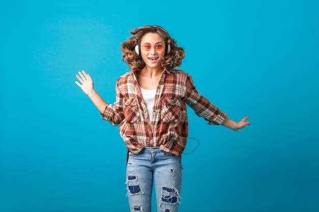Atrakcyjna uśmiechnięta emocjonalna kobieta skacząca z zabawnym szalonym wyrazem twarzy w kraciastej koszuli i dżinsach na białym tle na niebieskim tle studia, na sobie różowe okulary