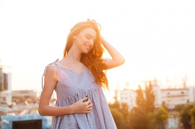 Atrakcyjna uśmiechnięta imbirowa kobieta w sukni pozuje z zamkniętymi oczami
