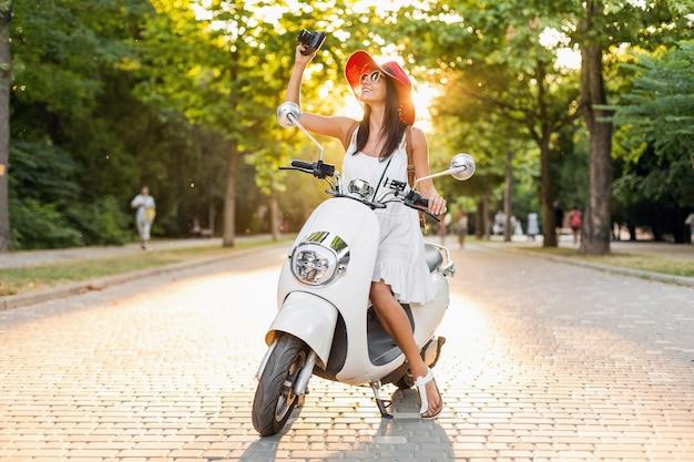 Atrakcyjna uśmiechnięta kobieta jeżdżąca na motocyklu na ulicy w letnim stroju na sobie białą sukienkę i czerwony kapelusz, podróżująca na wakacje, robienie zdjęć aparatem vintage