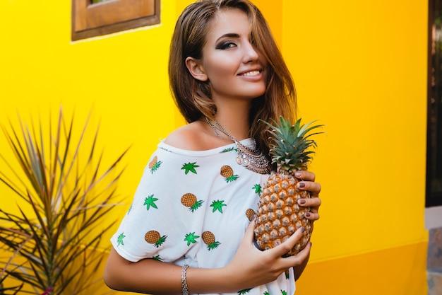 Atrakcyjna uśmiechnięta kobieta na wakacjach w t-shirt z nadrukiem moda letnia, trzymając się za ręce ananasa