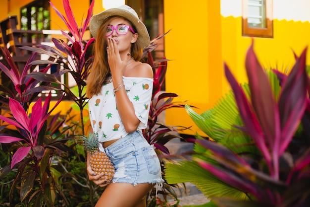 Atrakcyjna uśmiechnięta kobieta na wakacjach w t-shirt z nadrukiem słomkowy kapelusz moda lato, trzymając się za ręce ananasa