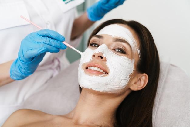 Atrakcyjna uśmiechnięta kobieta poddawana zabiegowi kosmetycznemu przez specjalistę leżąc w salonie kosmetycznym