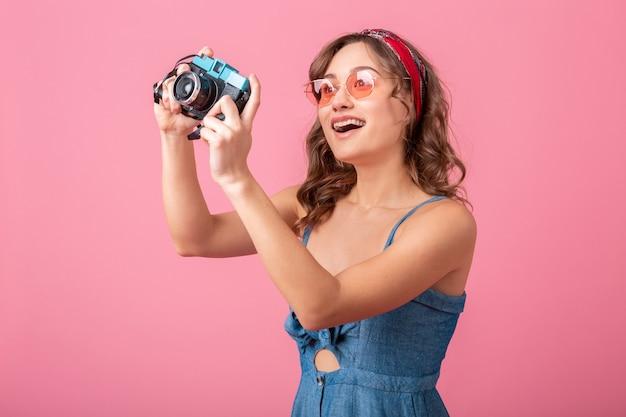 Atrakcyjna uśmiechnięta kobieta robienia zdjęć na vintage aparat na sobie dżinsową sukienkę i okulary przeciwsłoneczne, na białym tle na różowym tle
