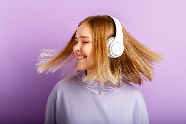 Atrakcyjna uśmiechnięta kobieta tańczy w słuchawkach z latającą blond fryzurą. nastolatek dziewczyna cieszyć słuchanie muzyki w ruchu w bezprzewodowych słuchawkach na białym tle nad fioletowy kolor tła.