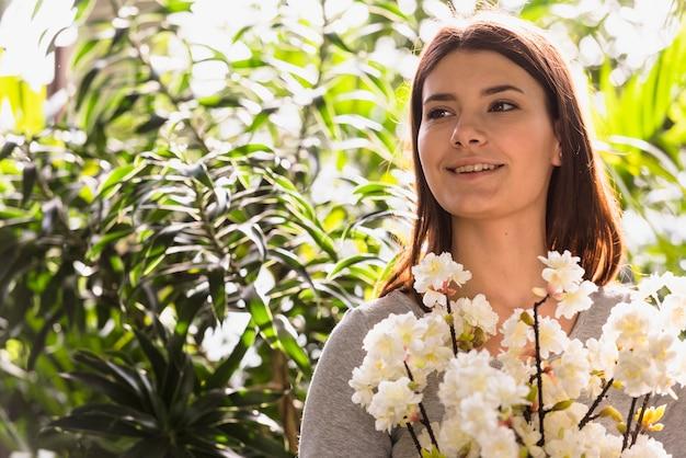 Atrakcyjna uśmiechnięta kobieta trzyma wiązkę kwiat kapuje