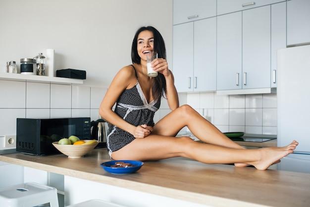 Atrakcyjna uśmiechnięta kobieta w piżamie jedząca rano śniadanie w kuchni, jedząca ciastka i pijąca mleko, zdrowy tryb życia, długie chude nogi